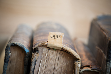 quizzes: Quiz concept text and old vintage books on a shelf Stock Photo