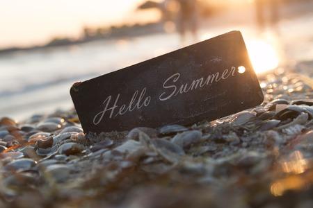 Hallo Sommer Inschrift auf dem Etikett, Sonnenuntergang am Strand.