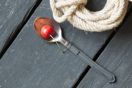 spoon with a cherry on an old black table