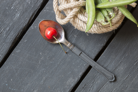 spoon with a cherry on an old black table and green beans