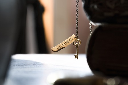 intercede: Key to Happiness - gold key on a chain, the Bible and inscription. Religion, Christianity, Orthodoxy idea. Stock Photo