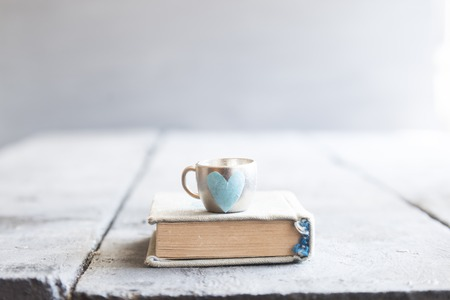 book on the table and a mug with a heart