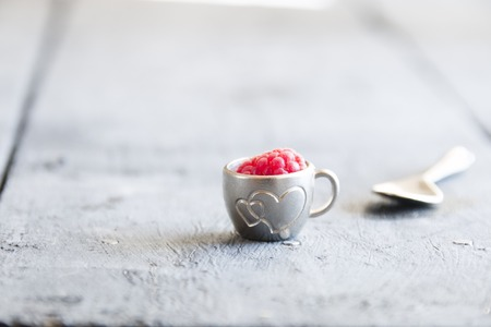 ripe raspberry in a cup on the table Stock Photo