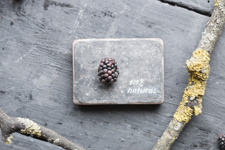 heathy diet: NATURAL inscription and blackberries on a wooden table. Stock Photo