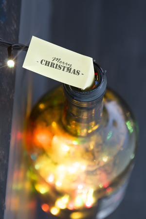 colored bottle: Merry Christmas idea, label and bottle with colored lights Stock Photo