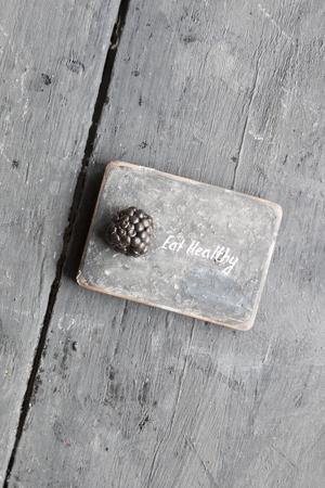 heathy diet: Eat heathy inscription and blackberries on a wooden table.