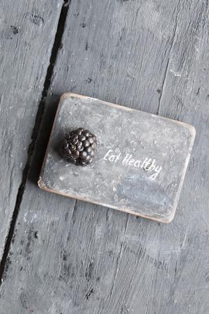 heathy: Eat heathy inscription and blackberries on a wooden table.