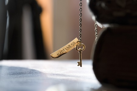 Key to Happiness - gold key on a chain, the Bible and inscription. Religion, Christianity, Orthodoxy idea. Stock Photo