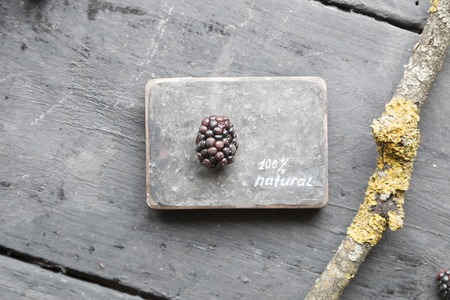 heathy diet: 100% NATURAL inscription and blackberries on a wooden table.