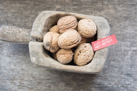 better: Eat Better Feel Better - text and walnuts on a rustic wooden table