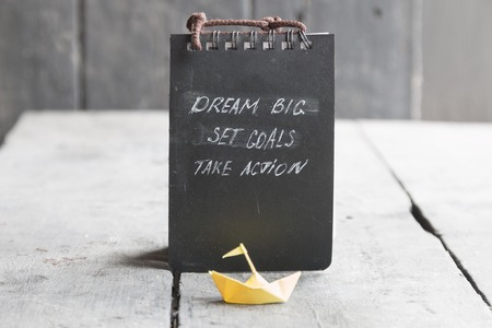 set goal: Dream Big - Set Goal - Take Action, handwriting on notebook cover, and a paper boat on an old table