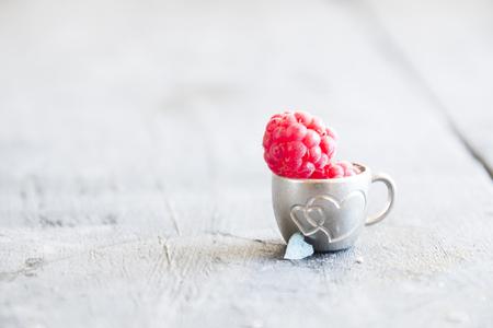 frambuesa madura en una taza en la mesa Foto de archivo