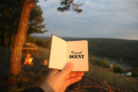 travel agent: Hand holding a book with the inscription travel agent