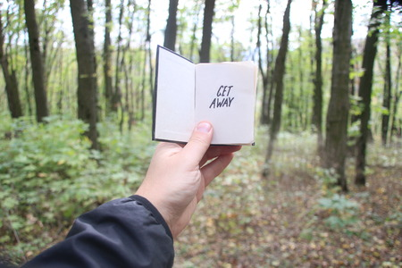 get away: Get Away idea, hand holding a book with text Stock Photo