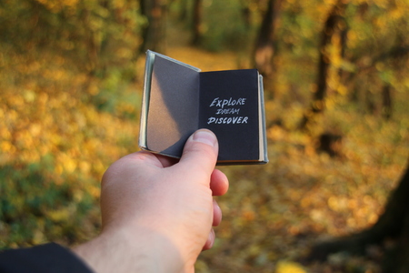 discover: Hand holding a book with the inscription Explore Dream Discover.