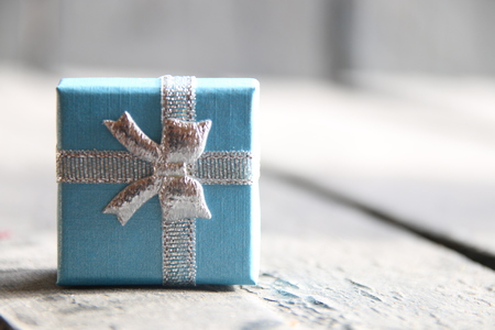 generosidad: Gift box with ribbon on vintage wooden background