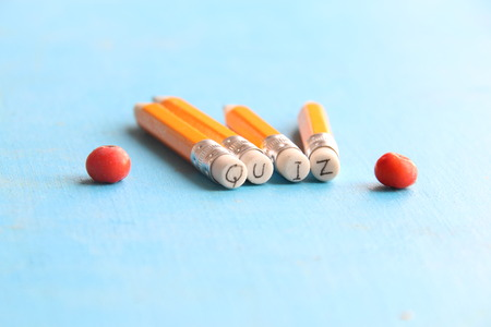 Quiz concept, yellow pencil on a blue table Stock Photo