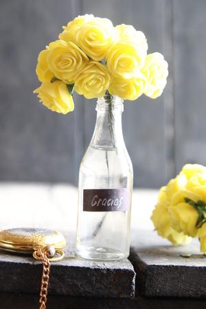 agradecimiento: Flores en una botella de vidrio y la etiqueta con la palabra Gracias español Foto de archivo