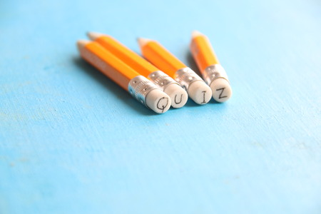 Quiz - inscription, yellow pencils and blue table. Stock Photo