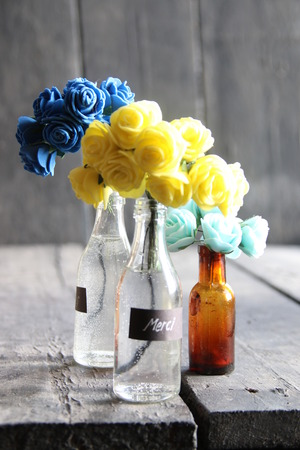 Merci tag and nice flowers in the bottles on wooden table Stock Photo