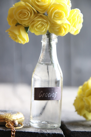 Gracias tag and Flowers in a glass bottle.