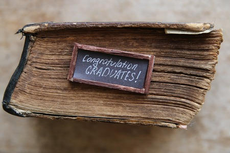 master degree: congratulations graduates text and vintage book on table Stock Photo