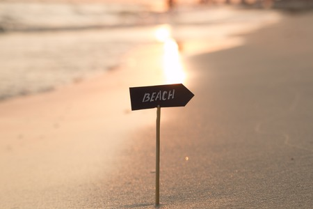 seascapes: Vacation or holidays concept - beach sign and sunset