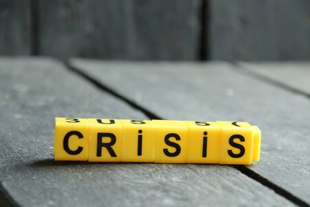crisis concept, word made of yellow cubes on vintage background