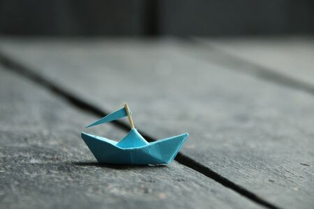 Ship with Flag, paper boat on an old vintage table.