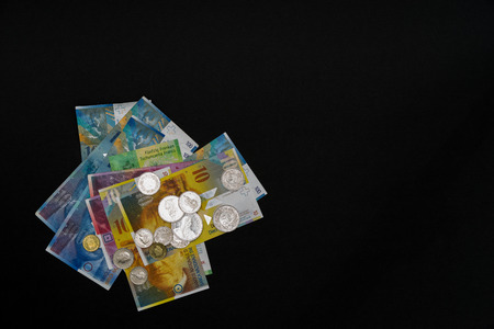 fidgety: Nine banknotes and coins arranged lying on each other on black background