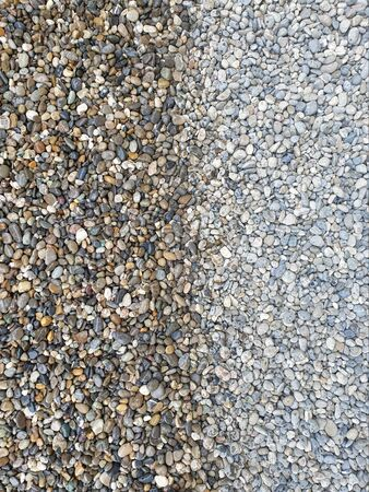 Colored, rounded and wet pebbles on the left and dry pebbles on the right where the color is not well emphasized as a background.