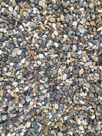 Colored, rounded and wet pebbles as a background.