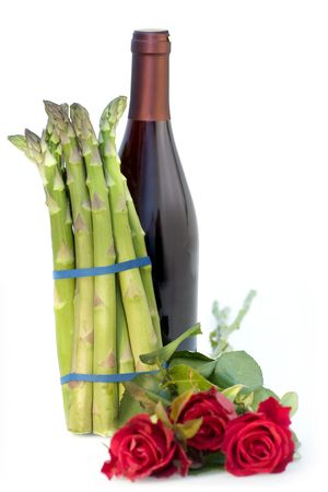 bunched: Still life of asparagus with roses and wine bottle