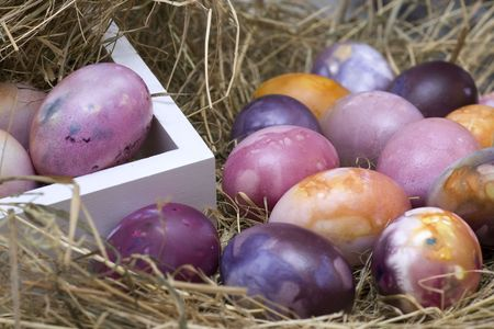 colored dye: Withe box in straw with colored easter eggs Stock Photo