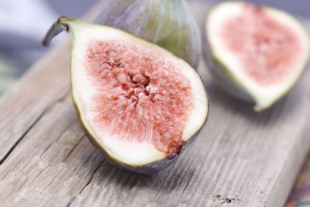 two and a half: Two half fresh figs on wood plate Stock Photo