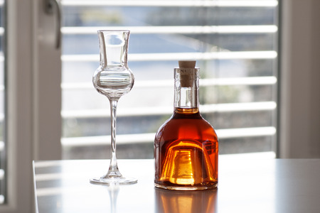 farbe: Brandy in a bottle with glass in front of modern background
