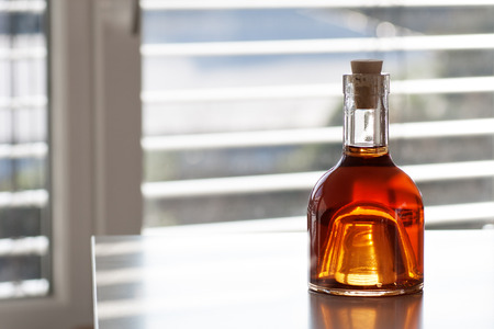 farbe: Brandy in a beautiful bottle in front of modern background