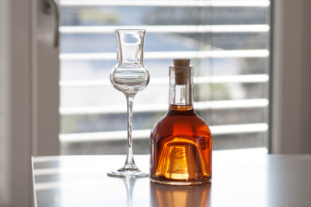 Brandy in a bottle with glass in front of modern background