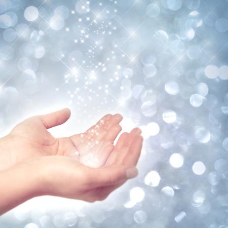 Hände fangen Stardust vor einem frostigen, winterlichen Hintergrund Standard-Bild - 43344595