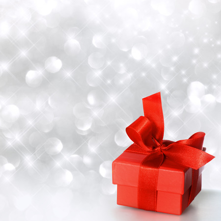 Gift box with ribbon in red with shiny silver background