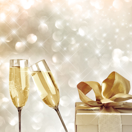 Toasting with champagne glasses very festive background with christmas gift Фото со стока