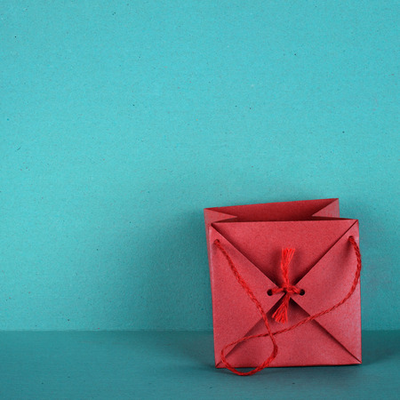 isoliert: Gift bag in red, is isolated on a background in turquoise Stock Photo