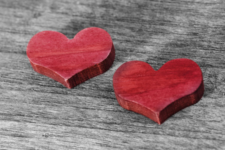Two red hearts on a wooden background