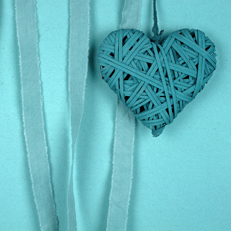 harmonie: A braided heart on a turquoise background of paper Stock Photo