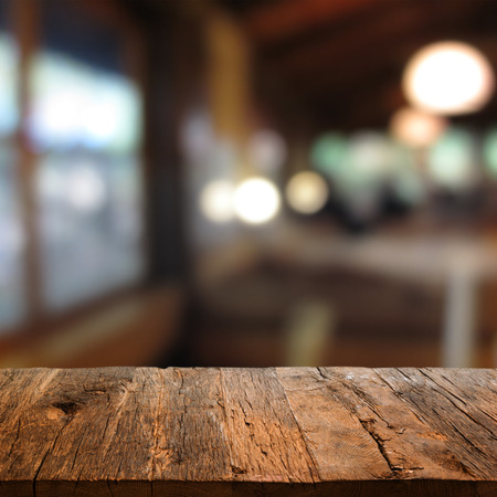 lights on: rustic wooden table with a view of evening restaurant backdrop