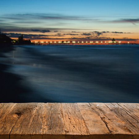 Wooden pier in the foreground, overlooking a seebrücke at night Фото со стока