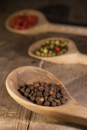 Top view of wooden spoon full of mixed colorful peppercorns Stock Photo