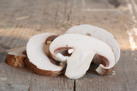 holz: Close up of a Sliced flat bottom Mushroom on a rustic chopping board.