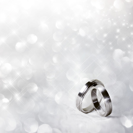 Wedding rings in front of festive background Stock Photo