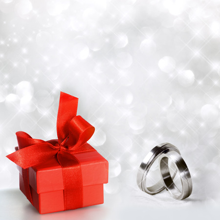 felicity: Wedding rings with red gift package in front of festive background Stock Photo